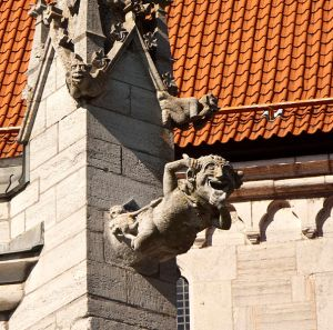 Gargoyle representing a comical demon at the base of a pinnacle with two smaller gargoyles, Visby, Sweden. Author: Alexandru Baboş  Albabo . Commons