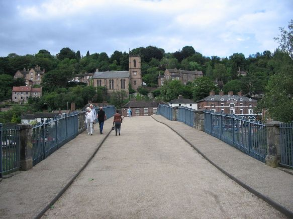 Pedestrians crossing the Iron bridge with Ironbridge in the background. Author: Boerkevitz at nl.wikipedia. Commons.
