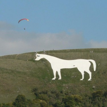 The Westbury White Horse, on the escarpment of Salisbury Plain. It is the oldest of several white horses in Wiltshire. There is no evidence of its existence before 1742. Author Chris Downer, whilst paragliding. Two people are standing on the horse for scale. Creative Commons
