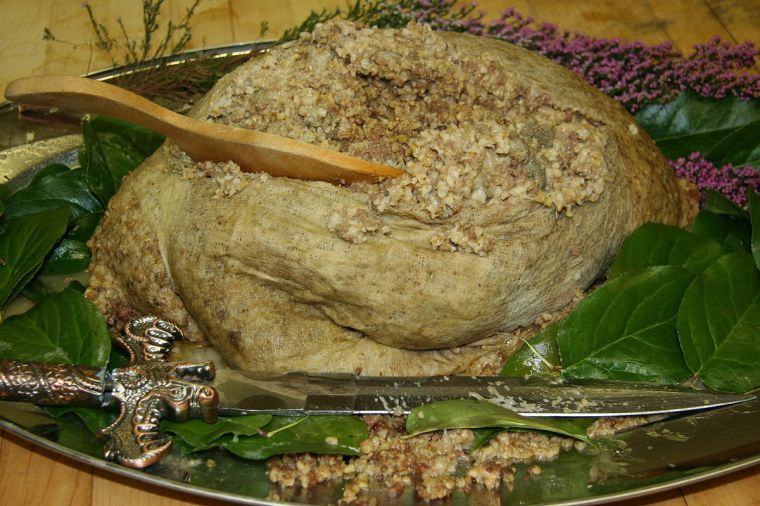"Haggis on a garnished platter with a knife used to cut it open in the ""Address"" to a haggis at a Burns Supper in Rochester, Minnesota. Author: Jonathunder. Creative Commons"