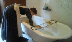 Maid running a bath for one of the guests