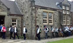 Costumed schoolchildren filing in for their lesson
