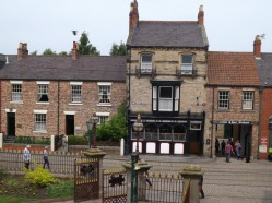 Pub, livery stables and houses opposite the park