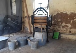 Mangle, dolly tub and buckets inside the wash house